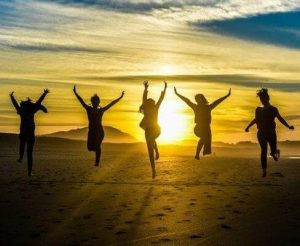 girls jumping up in sunset